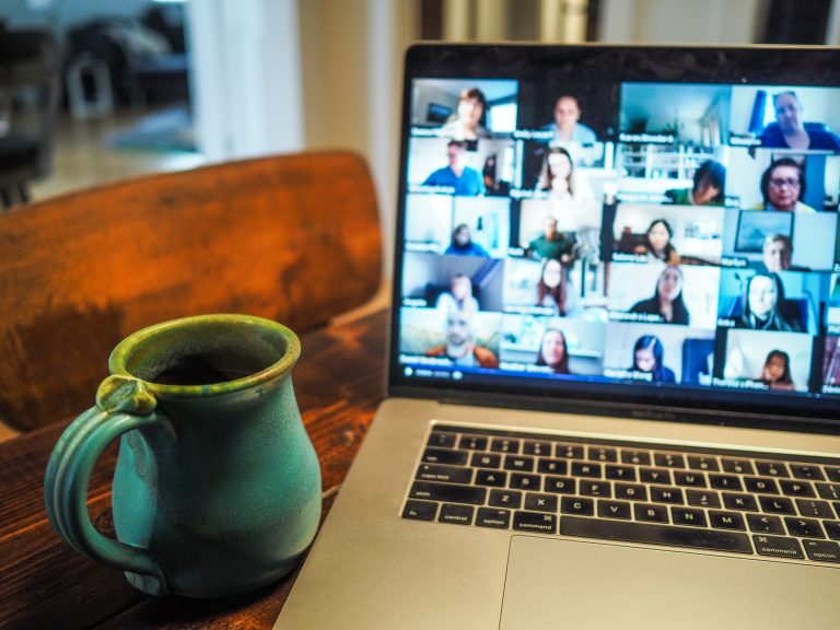 Cup next to a computer screen displaying the participants of an online meeting.