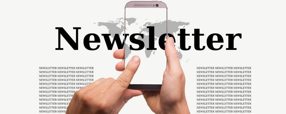 Hands holding mobile phone with Newsletter